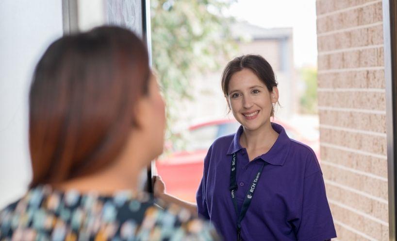 Two women talking at front door