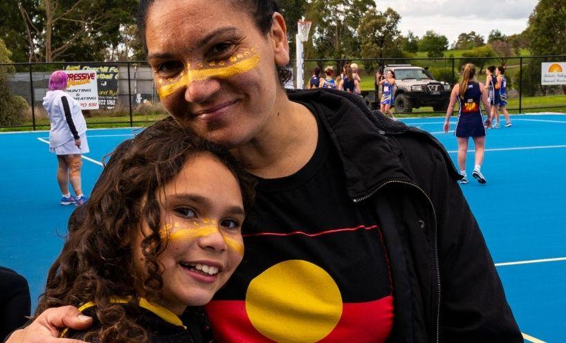 Mum in Aboriginal flag shirt and daughter at netball