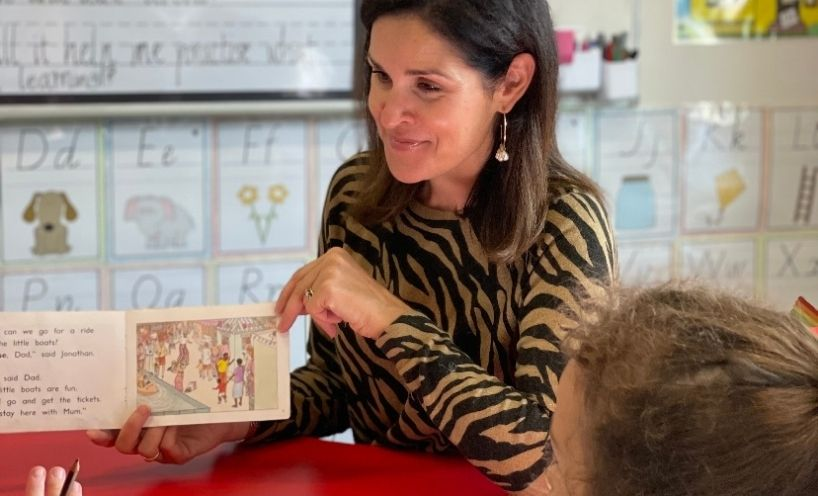 Primary teacher reading a picture book