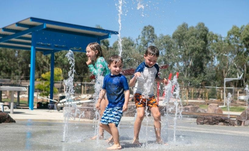Three children play in water All Abilities Playspace