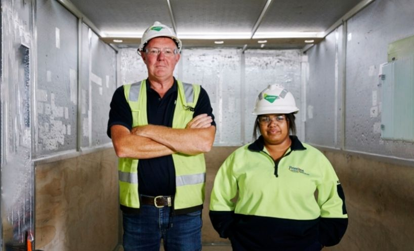 Two healthcare workers wearing hi-vis and hard hats