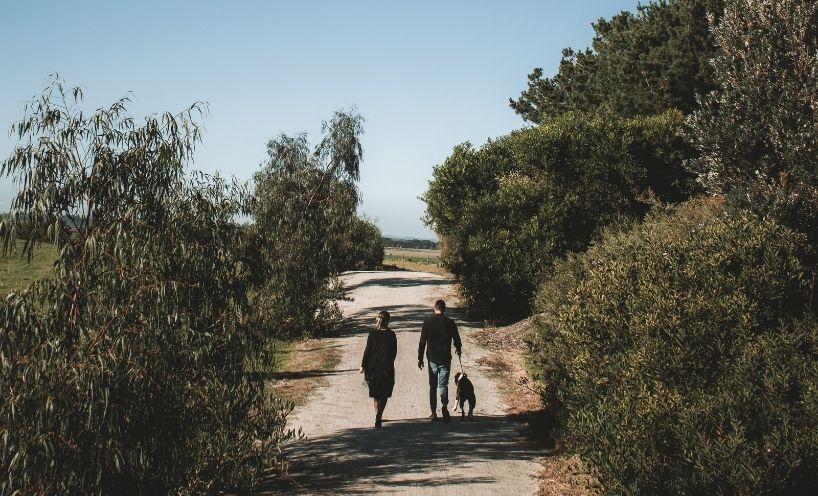 Woman and man walking dog on a dirt path at Venus Bay